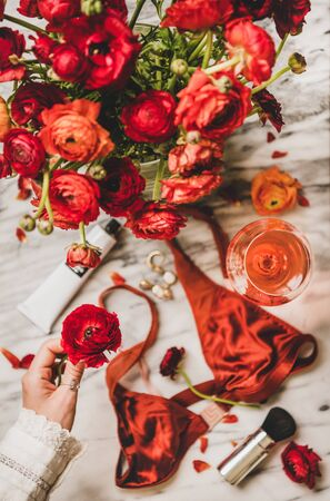 Female care beauty things. Flat-lay of silk lingerie, cosmetics, cream, jewelry, glass of rose wine and womans hand with red flower over marble table, top view. Feminine attributes and beauty rituals
