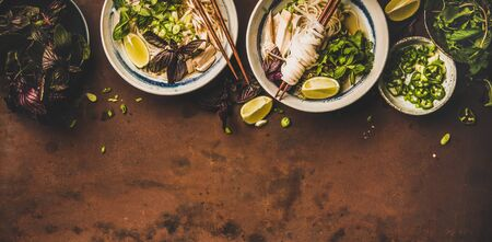 Rice noodle chicken soup Pho Ga with cilantro, soy sprouts, greens, lime in bowls with chopsticks over rusty