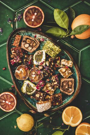 Flat-lay of variety of Turkish traditional lokum sweet delight in plate and fresh fruits over green Moroccan tile table, top view. Middle East typical dessert