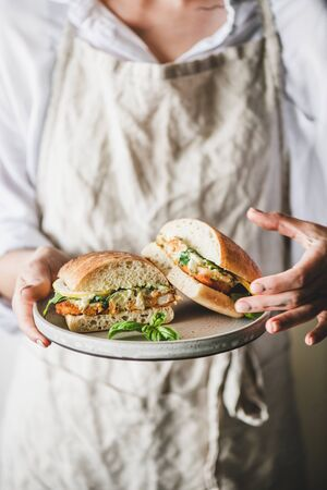 Woman in beige linen apron holding fresh fried fish sandwich with tartare sauce, lemon and arugula cut in halves on plate, selective focus. Healthy easy breakfast ideas