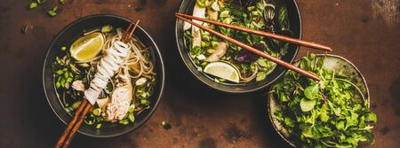 Asian cuisine lunch. Flat-lay of Vietnamese rice noodle chicken soup Pho Ga with cilantro, soy sprouts, fresh greens, lime in bowls with chopsticks over dark background, top view, wide composition