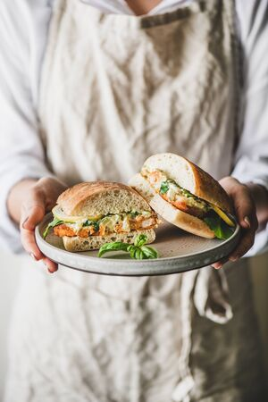 Woman in linen apron holding fresh fried fish sandwich with tartare sauce, lemon and arugula cut in halves on plate in hands, selective focus. Healthy easy breakfast ideas