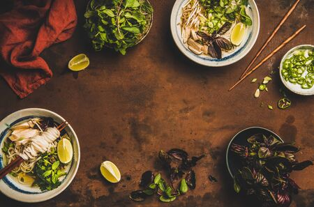 Vietnamese cuisine lunch. Flat-lay of rice noodle chicken soup Pho Ga with cilantro, soy sprouts, greens, lime in bowls with wooden chopsticks over rusty background, top view, copy space