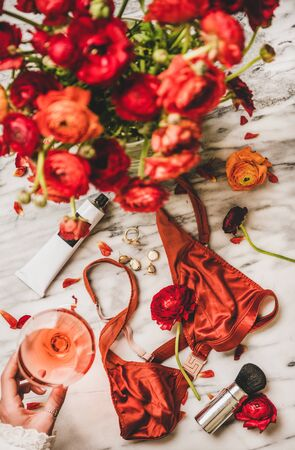 Female care beauty things. Flat-lay of silk lingerie, cosmetics, cream, jewelry, red flowers and womans hand with glass of rose wine over marble table, top view. Feminine attributes and beauty rituals