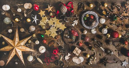 Christmas, New Year holiday layout background, texture, wallpaper. Flat-lay of decorative objects, fur tree toys, garlands, ropes, wreaths over wooden background, top view. Winter holidays preparation Imagens