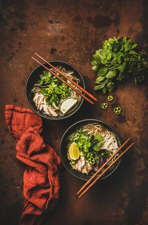 Asian cuisine lunch. Flat-lay of Vietnamese rice noodle chicken soup Pho Ga with cilantro, soy sprouts, fresh greens, lime in black bowls with chopsticks over dark background, top view. Healthy food