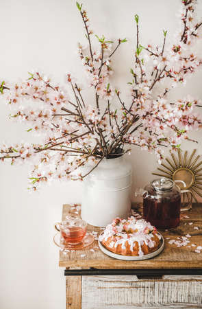 Spring or summer tea and cake setting. Rose and almond gluten-free bundt cake with rose flowers and black tea on rustic wooden cupboard under almond blossom branches in vase, white wall background
