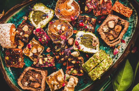 Flat-lay of variety of Turkish traditional lokum sweet delight in plate over green Moroccan tile table, top view, close-up. Middle East typical dessert Banco de Imagens