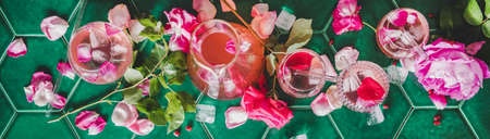 Summer refreshing cold beverage drink. Flat-lay of rose lemonade with ice in glasses and rose flower petals over green tile table background, top view, wide composition 写真素材