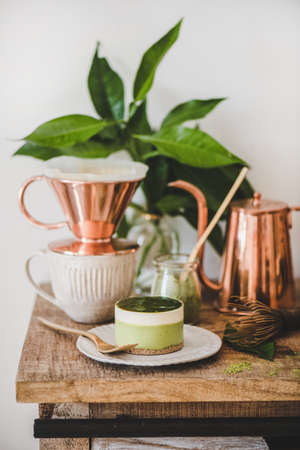 Coffee and dessert setup. Green matcha cheesecake and brewed black coffee in copper pot on rustic wooden kitchen counter, white wall background, close-up. Healthy, vegan, vegetarian, low calorie food