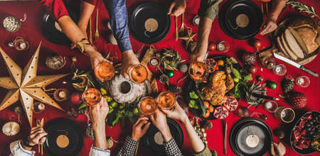 Family celebration Christmas, New Year. Flat-lay of people clinking glasses with champagne over table with red cloth with roasted turkey, bundt cake, fruit, decorations, top view, wide composition