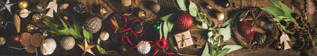 Christmas, New Year holiday background, texture, wallpaper. Flat-lay of decorative objects, fur tree toys, garland, ropes, candles, glass balls, wreaths over rustic wooden background, wide composition Archivio Fotografico