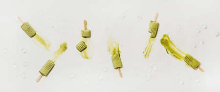 Green matcha coconut vegan ice cream  . Flat-lay of melting matcha  over plain white table background with ice, top view. Summer healthy dessert, clean eating, dairy free food concept