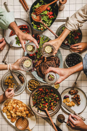 Summer barbeque party. Flat-lay of table with grilled meat, vegetables, salad, roasted potato and peoples hands feasting over checkered tablecloth, top view. Family gathering, comfort food concept