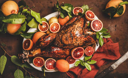Christmas or Thanksgiving Day festive table setting. Whole roasted turkey with citrus fruit over rusty table background, top view, selective focus. Holiday gathering food concept Stock fotó - 155447005