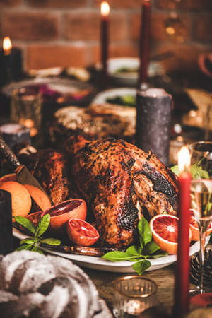 Family or friends celebrating Christmas or New Year. Holiday rustic wooden table with roasted turkey, chocolate cake and candles, red brick wall at background, selective focus Stock fotó - 155447030