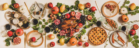 Autumn Thanksgiving, Friendsgiving or family party gathering celebration table setting. Flat-lay of Fall table with roasted duck, vegetables, cheese board, apple pie with pumpkins, fruit and leaves