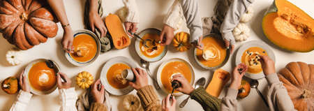 Healthy autumn comfort food for family gathering. Flat-lay of peoples hands eating fall seasonal pumpkin cream soup served in plates on white table decorated with fresh colorful pumpkins, top view