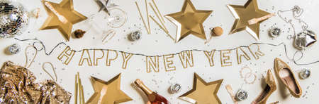 Flat-lay of Happy new year golden lettering, party Discoball, traditional golden and silver glitter decorations, shoes, dress, bag and champagne bottle over white background