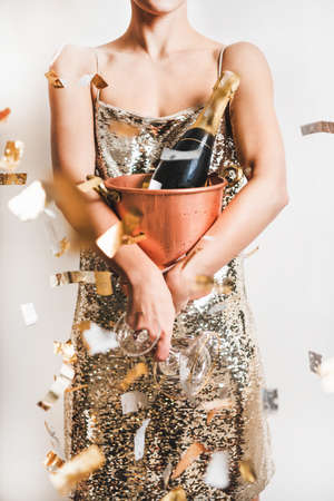 Young woman figure in festive glittering cocktail golden mini dress holding copper bucket with ice for champagne bottle and glasses over white wall with confetti. New Year holiday party concept