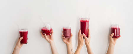Human hands holding glasses and jar with purple beet pomegranate fresh smoothie with glass straws over white wall background