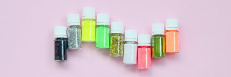 Colorful glitters lies on pastel pink background. Many round jars with multi-colored bright sparkles for nail polish. Sparkling sequins
