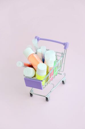 The shopping cart is filled with many round jars with multi-colored bright sparkles for nail polish. Sparkling sequins Imagens