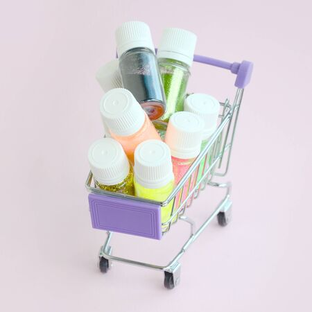 The shopping cart is filled with many round jars with multi-colored bright sparkles for nail polish. Sparkling sequins 写真素材