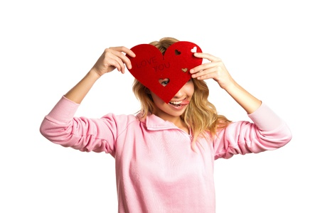 pretty s shiny: Attractive girl holding red heart-shaped decoration and hiding her eye Stock Photo