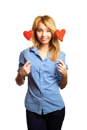 sexual selection: Attractive blonde girl holding red heart-shapes and smiling Stock Photo