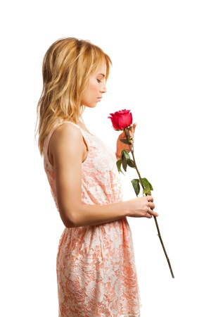 Attractive young woman holding a flower in her hands photo