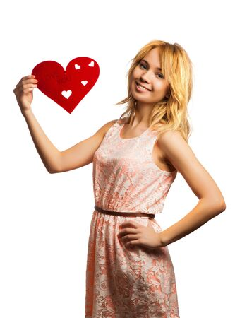 Attractive young woman holding red heart-shape and smiling photo