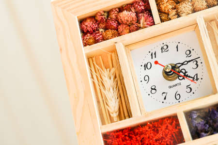 Stylish wooden clock with a various flower accessories inside the frame photo