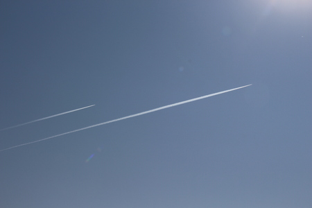 A trail of a jet in the blue sky  A high-flying aircraft in the sky  A clear day Banco de Imagens