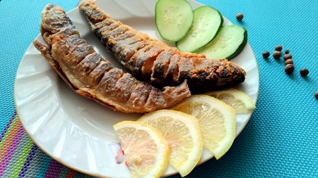 Fried sea fish on a plate  Fried fish, lemons and cucumbers  Ready-to-eat seafood and pepper