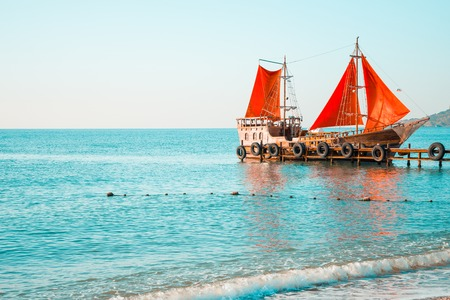 Wooden ship with red sails at a sea pier