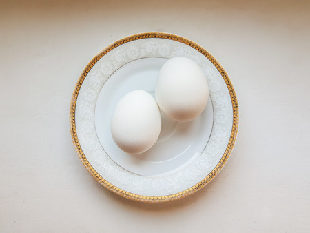 Two white eggs on a saucer with a gold frame. Top view.