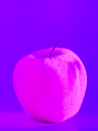 One apple on the table. Neon light.