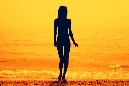 Silhouette of a skinny young girl walking along the beach
