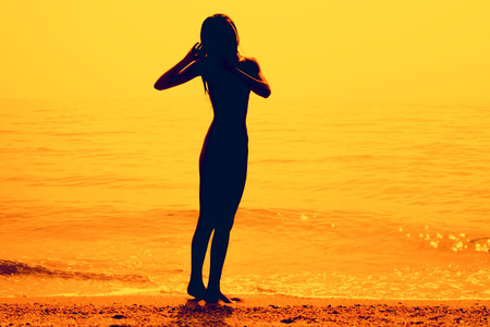 Silhouette of a slim young girl walking along the beach, pink tone.