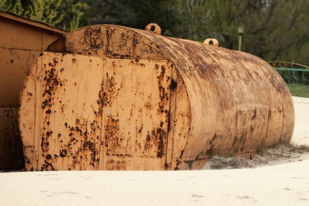yellow rusty abandoned tank lying on the beach. Stockfoto