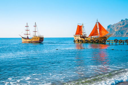 Two old wooden ships. One of them with red sails is on the pier. Scarlet sails, as in the famous story of Alexander Green. The second sails from the pier without raised sails. Koktebel, Crimea. Stock Photo