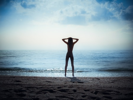 silhouette of slim girl on the sea beach, hands by head Banque d'images