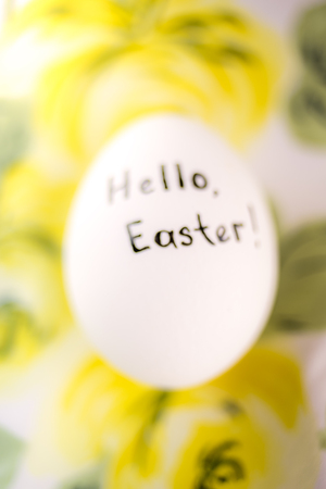 White chicken egg with black inscription hello easter on a yellow floral background