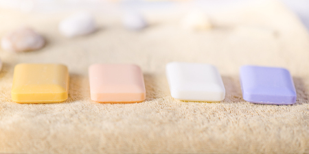 Four solid pieces of soap lie on a pale brown towel. Sea shells in the back. Side view with beautiful light. Imagens