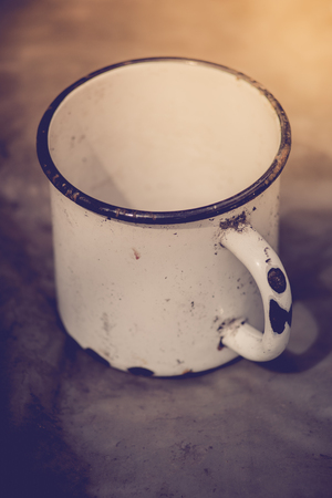 Large white enamelled mug with damaged enamel.