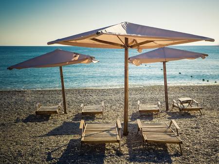 Parasols en houten strandbedden op het zeekiezelstrand Stockfoto