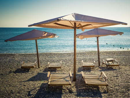 Sun umbrellas and wooden beach beds on the sea pebble beach Reklamní fotografie