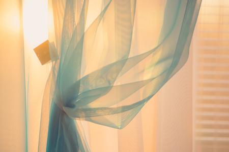 Sol a la luz del atardecer a través de las finas cortinas de la ventana con persianas