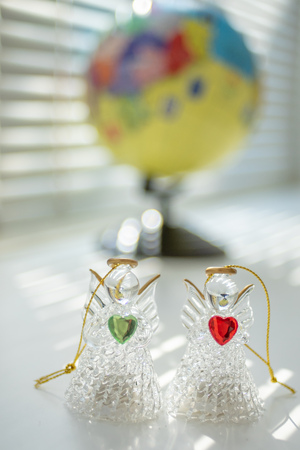 Two angels, messengers of peace and love on the background of the globe 版權商用圖片